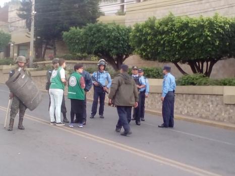 Observadores dialogan con militares y policías, mientras detrás de cerco militar miles gritan consignas.